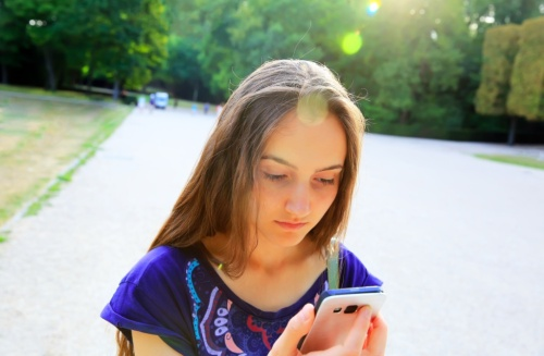 Girl with a mobile phone reads the message in the park